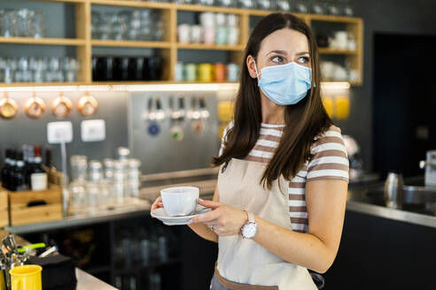 Thoughtful young owner wearing mask while holding coffee cup and saucer in cafe - GIOF08587