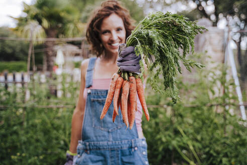 Smiling mid adult woman holding carrots while standing in vegetable garden - EBBF00427