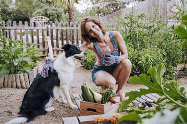 Smiling woman holding water bottle crouching by border collie in vegetable garden - EBBF00430