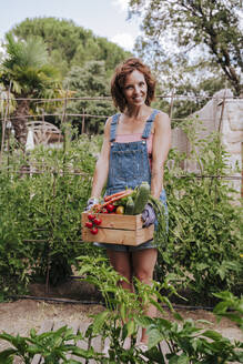 Smiling woman holding various vegetables in crate while standing against plants at community garden - EBBF00436