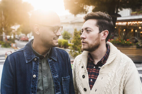Close-up of gay couple looking at each other while standing in city - DSIF00030