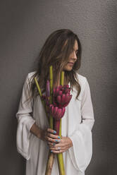 Mid adult woman holding bouquet while standing against wall - DSIF00051