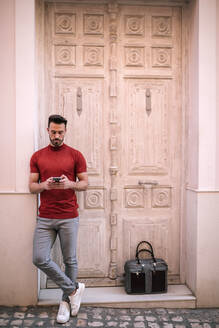 Businessman using mobile phone against closed door - GRCF00294