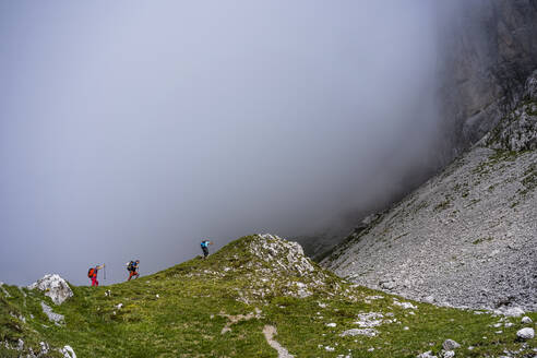 Male hikers walking on mountain during foggy weather at Bergamasque Alps, Italy - MCVF00532