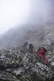 Mature men climbing on mountain during foggy weather, Bergamasque Alps, Italy - MCVF00535