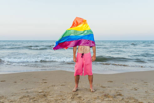 Man standing on the beach with gay pride flag covefring his face - CJMF00310