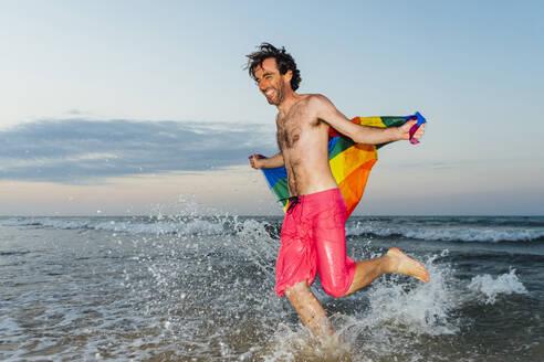 Laughing man running in splashing water, carrying gay pride flag - CJMF00313
