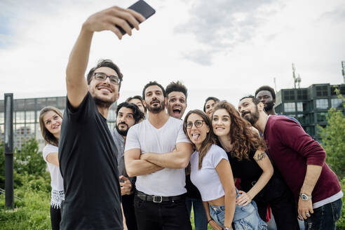Cheerful man taking selfie with group of friends in park against sky - MEUF01525