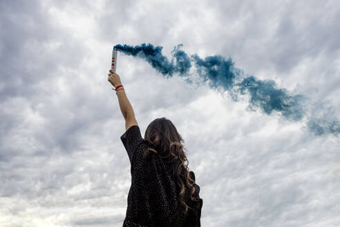 Young woman holding smoke bomb against cloudy sky - MEUF01540