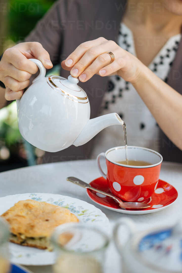 Crop View Of Female Holding Porcelain Teapot And Pouring Hot Tea Into Red Ceramic Polka Dotted