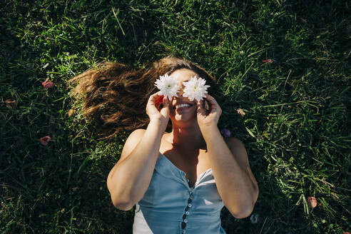 Young woman holding flowers over face while relaxing on grassy land in park - DCRF00466