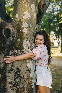 Smiling young woman with eyes closed embracing tree trunk while standing in park - DCRF00478