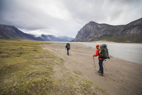 Rear view of backpackers traversing Akshayak Pass - CAVF87356