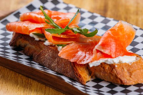 Close-up view of delicious slices of salmon with potherb placed on slice of bread with cream cheese on checkered board on wooden table - ADSF02570