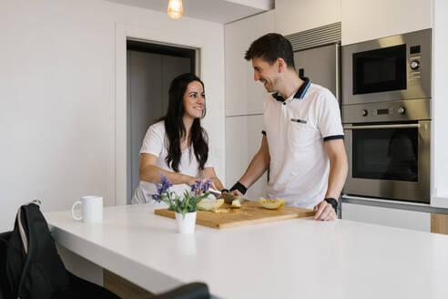 Smiling woman looking at man while cutting fruit at kitchen island - EGAF00451