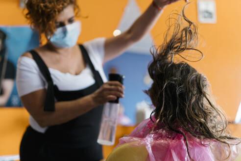 Female hairdresser spraying water on girl's brown hair at barber shop - EGAF00467