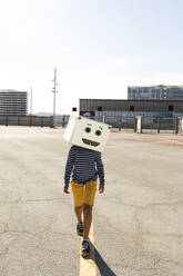 Boy wearing robot mask walking on street against clear sky during sunny day - VABF03139