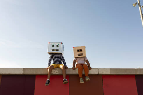 Friends wearing robot masks sitting on retaining wall against clear blue sky - VABF03142