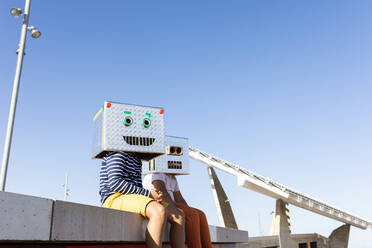 Boys wearing robot masks made of boxes while sitting on retaining wall against clear blue sky - VABF03145