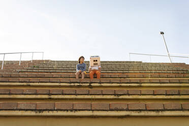 Boy wearing robot mask sitting with friend on steps against sky during sunny day - VABF03148