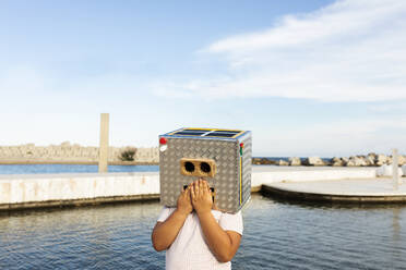 Boy with hands on mouth of robot mask standing by the water against sky - VABF03151