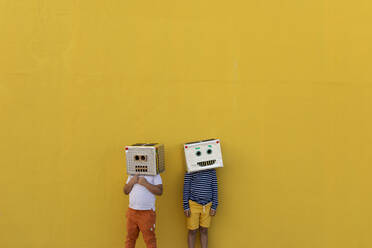Boys wearing robot masks made of boxes while standing against yellow wall - VABF03154