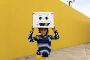 Boy wearing robot mask while standing against yellow wall - VABF03157