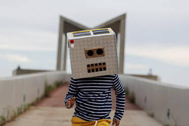 Boy wearing robot mask made of box running on footpath against sky - VABF03160