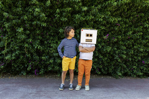 Boy looking at friend wearing robot mask while standing against plants on road in park - VABF03163