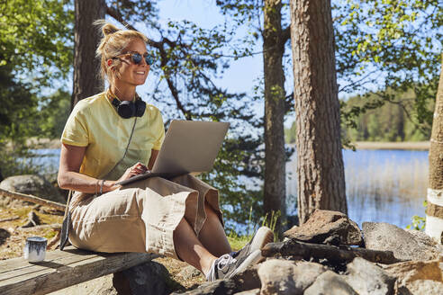 Mid adult woman wearing sunglasses using laptop while sitting in Tiveden National Park, Sweden - UKOF00011