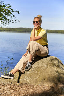 Smiling woman wearing sunglasses sitting on rock against lake in Tiveden National Park, Sweden - UKOF00014