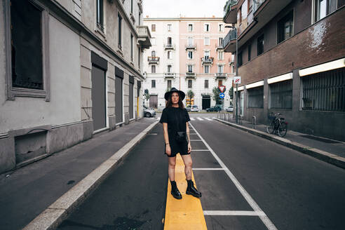 Young woman wearing hat standing on road amidst buildings in city - MEUF01606