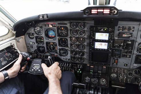 Unrecognizable man in headset piloting plane?alone while sitting in cockpit of modern aircraft - ADSF03108