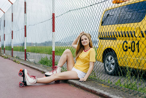 Pretty cheerful teen girl wearing shorts with roller skates and sitting on ground smiling at camera. - ADSF03394