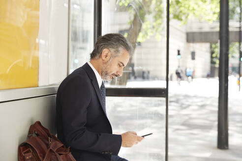 Businessman using phone while sitting at bus stop - PMF01224