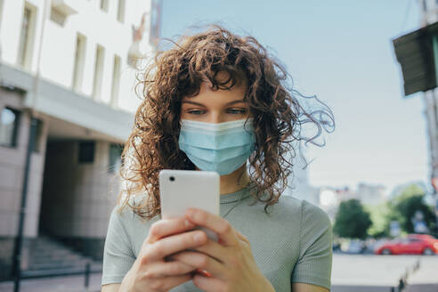 Woman wearing protective mask and using smartphone in city - OYF00153
