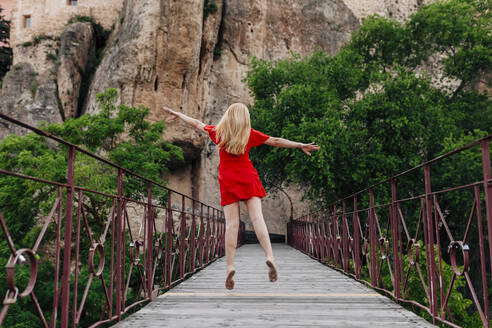 Ballerina walking and dancing over Saint Paul Bridge in Cuenca, Spain - MRRF00139