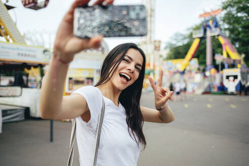 Happy young woman gesturing while taking selfie in amusement park - OYF00177