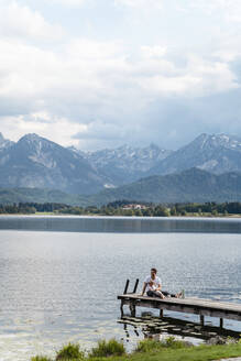Father with daughter sitting on jetty over lake against mountains and cloudy sky - DIGF12765
