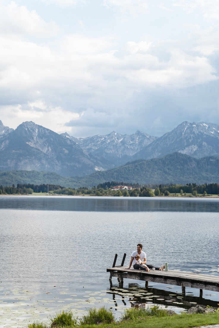 Father with daughter sitting on jetty over lake against mountains and cloudy sky - DIGF12765 - Daniel Ingold/Westend61