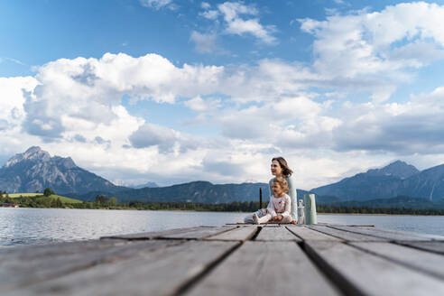 Mother and daughter sitting on jetty over lake against cloudy sky - DIGF12768
