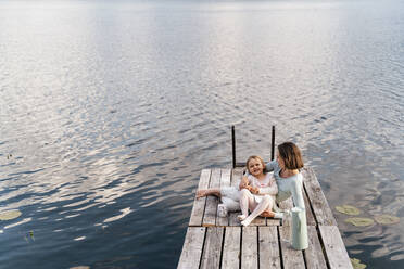 Mid adult woman and daughter relaxing on jetty over lake - DIGF12771