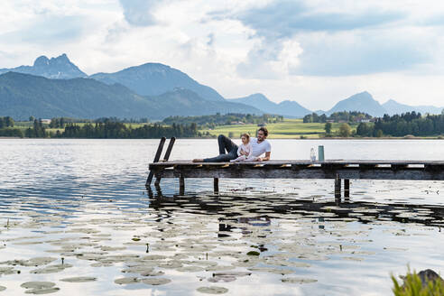 Father and daughter looking at view while relaxing on jetty over lake against mountains - DIGF12774