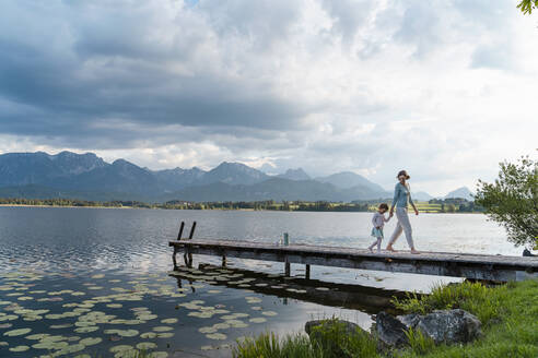 Mother and daughter holding hands while walking on jetty over lake against cloudy sky - DIGF12780