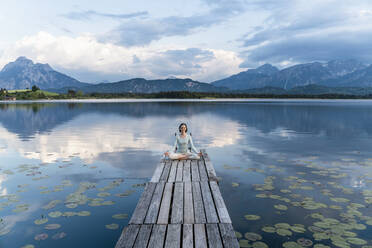 Woman meditating while sitting on jetty over lake against cloudy sky - DIGF12786
