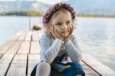 Close-up of cute girl wearing tiara sitting on jetty against lake - DIGF12792