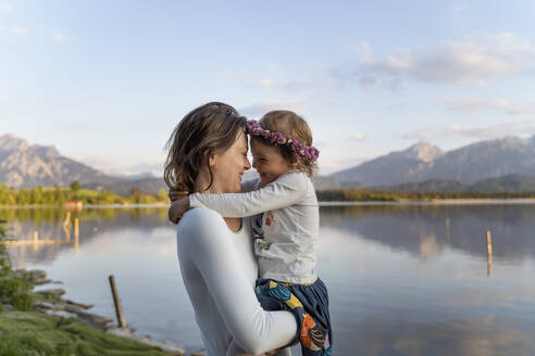Mother carrying cheerful daughter while standing by lake against sky during sunset - DIGF12798