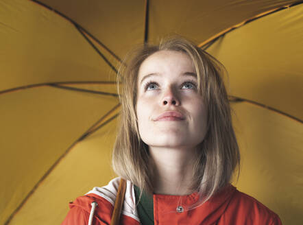 Close-up of young woman with yellow umbrella looking up in city - HPSF00035