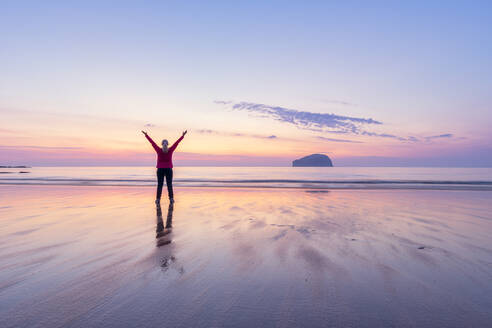 Mature woman with arms raised standing at Seacliff Beach during sunset, North Berwick, Scotland - SMAF01938