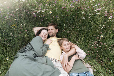 Smiling parents with son lying on land amidst flowers - EYAF01221